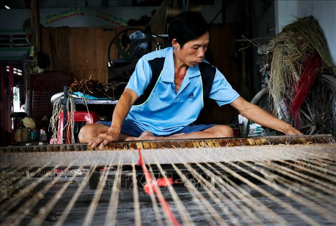 Photo: A craftsman weaves a sedge mat manually with his loom. VNA Photo: Nam Thái
