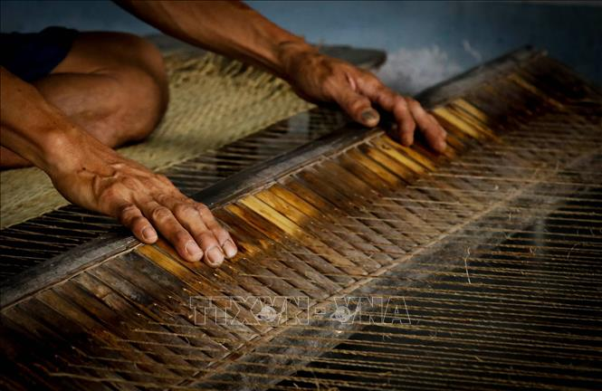 Photo: Skillful and rough hands of a craftsman weaving sedge mat on traditional loom. VNA Photo: Nam Thái