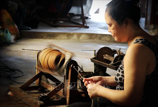 Photo: A craftswoman in Long Dinh village spins sedge fibers into thread for weaving. VNA Photo: Nam Thái
