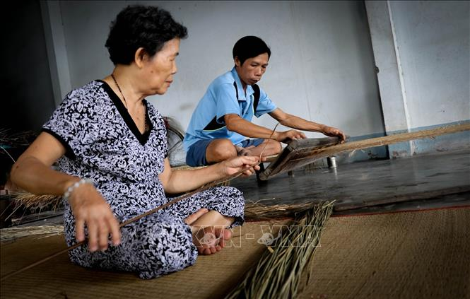 Photo: Various families in Long Dinh village still preserve traditional mat weaving techniques through making mats manually. VNA Photo: Nam Thái