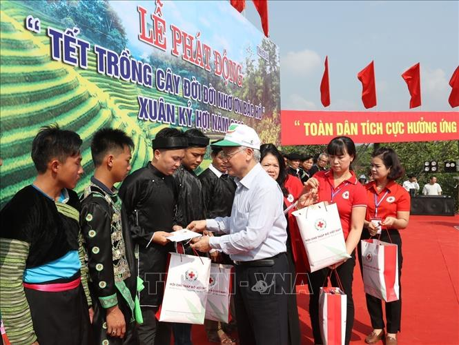 Photo: Party General Secretary, President Nguyen Phu Trong presents Tet gifts to disadvantaged families of Tran Yen district. VNA Photo: Trí Dũng