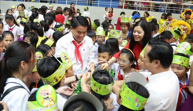 Photo: Chairman of the Hanoi People's Committee Nguyen Duc Chung gives mid-autumn gifts to children at the programme. VNA Photo