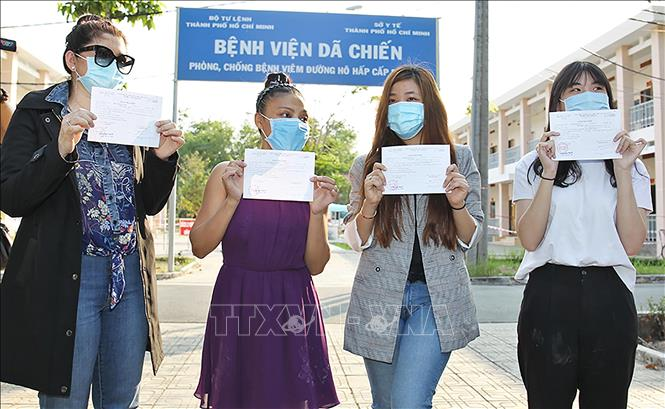 Photo: The four COVID-19 patients with their certificates of discharge from the hospital. VNA Photo: Đinh Hằng