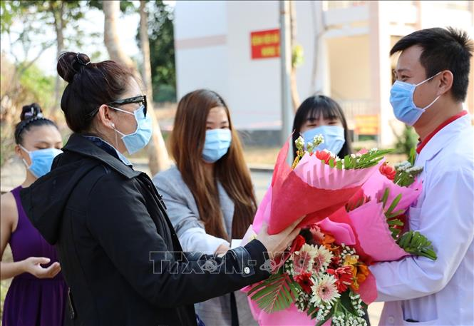 Photo: The four COVID-19 patients present flowers to doctors and nurses of the hospital. VNA Photo: Đinh Hằng