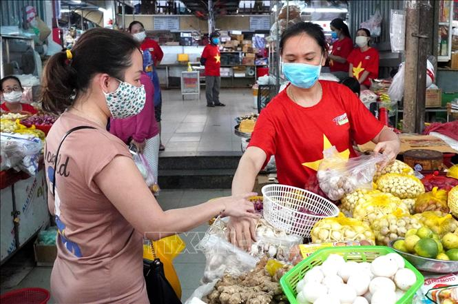 Photo:  Most of merchants in Da Nang city wear national flag t-shirts in the fight against COVID-19 pandemic. VNA Photo: Quốc Dũng