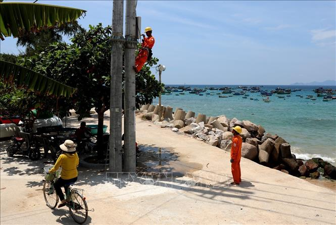 Photo: Workers access households in Nhon Chau island, the central province of Binh Dinh to electricity. VNA Photo: Ngọc Hà