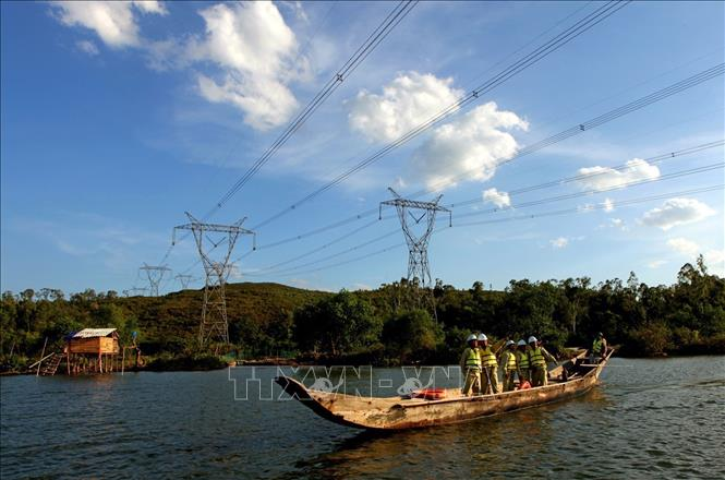 Photo: Workers check the transmission line in the central province of Quang Binh. VNA Photo: Ngọc Hà